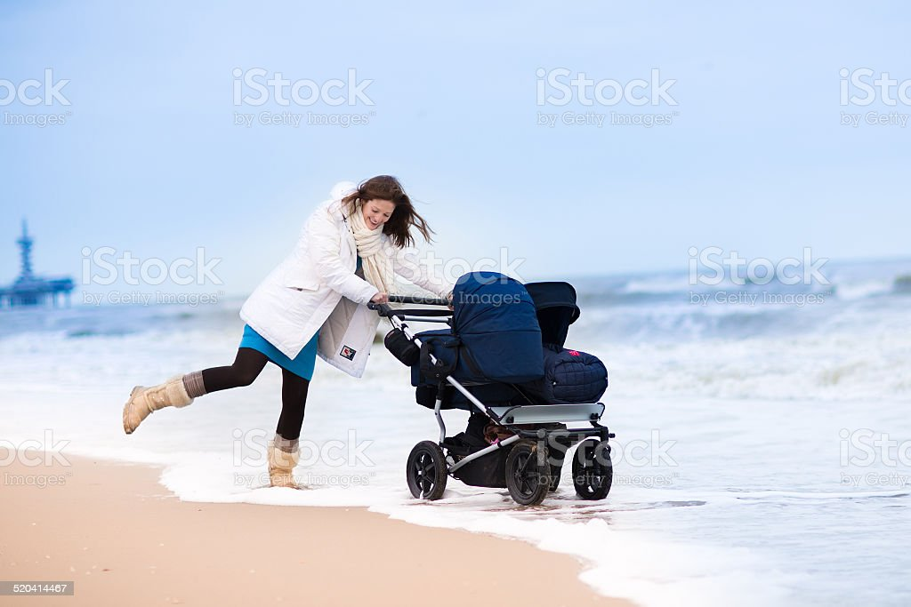 Happy active young mother walking on beach with double stroller stock photo