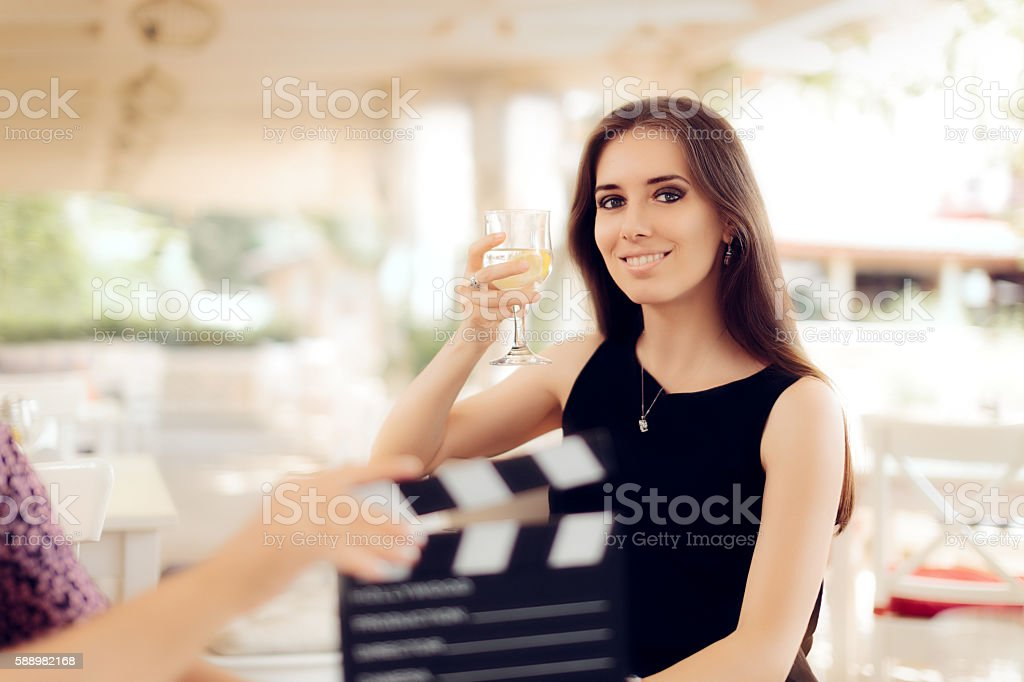 Happy Actress Holding a Glass in Movie Scene stock photo