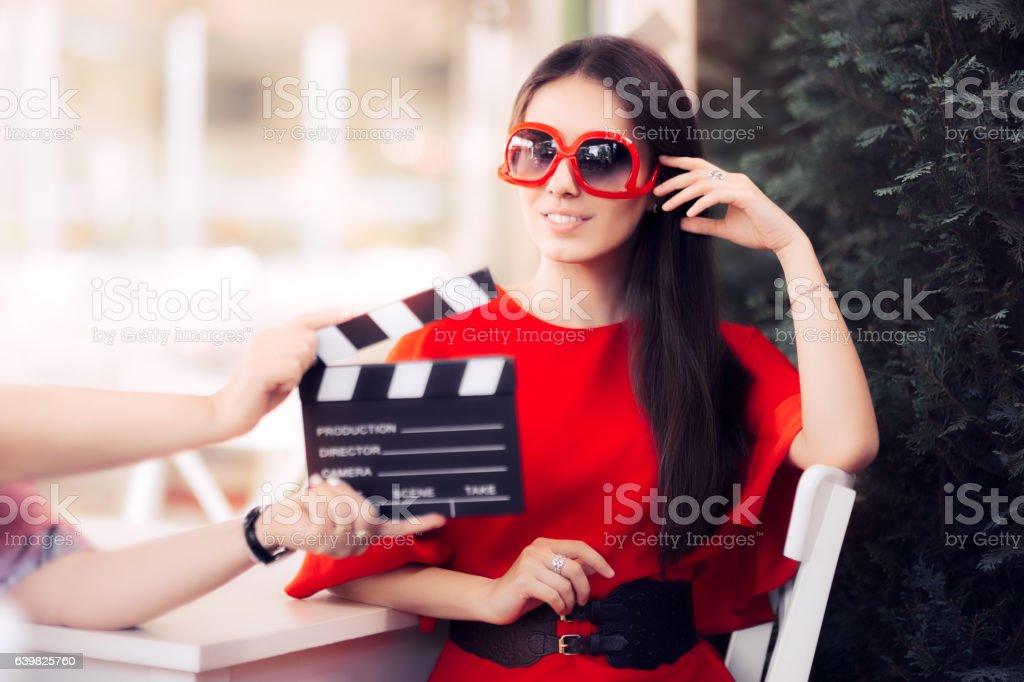 Happy Actress with Oversized Sunglasses Shooting Movie Scene stock photo