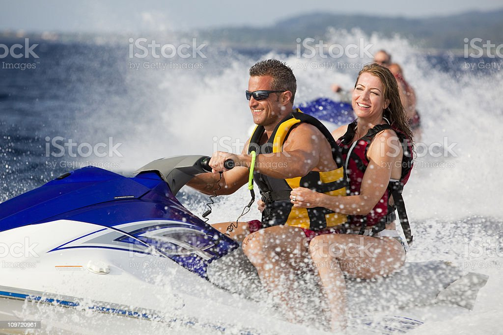 Happy adult couple enjoying ride on jetski stock photo