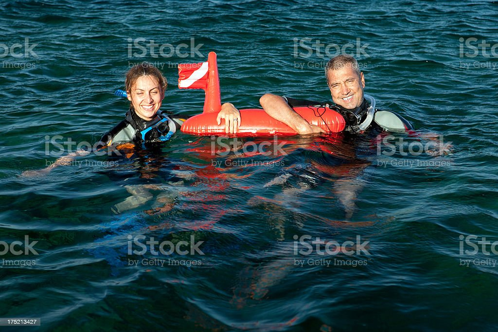 Happy Adult Couple holding a buoy into the water royalty-free stock photo