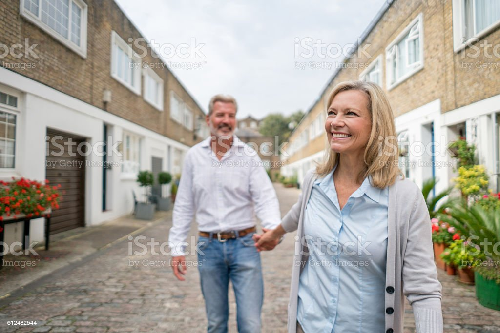 Happy adult couple holding hands stock photo