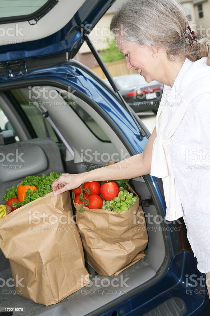 Happy Adult Woman Picking Up Her Groceries royalty-free stock photo