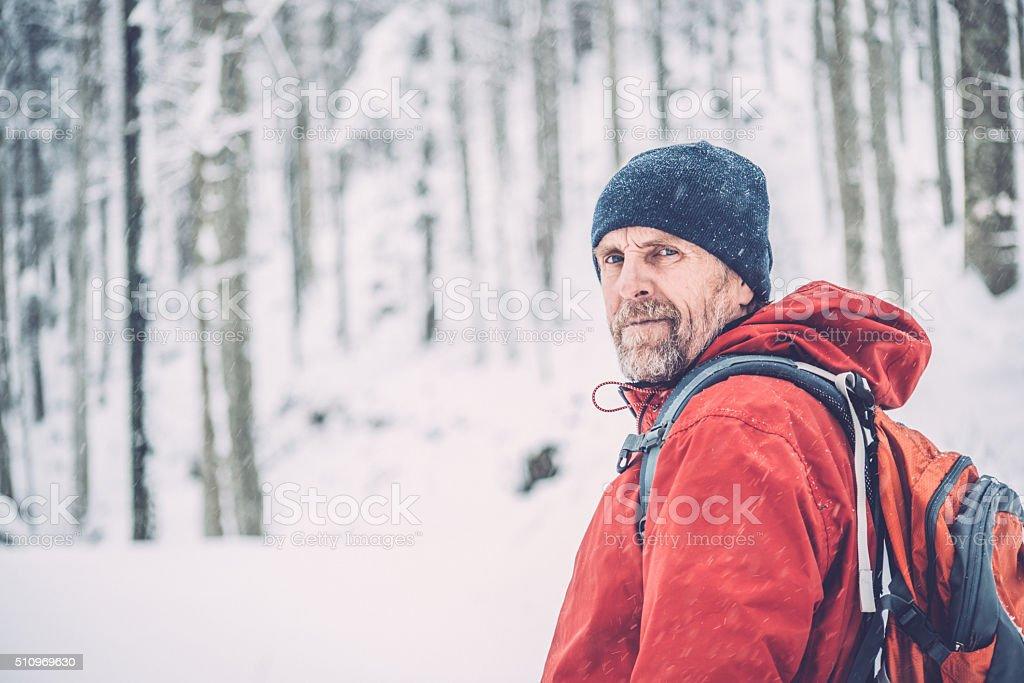 Happy Adventurous Senior Man Hiking in Forest, Snowing,  Alps, Europe stock photo
