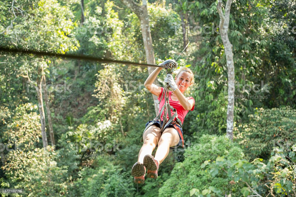 Happy adventurous woman on a zip-line crossing the jungle stock photo