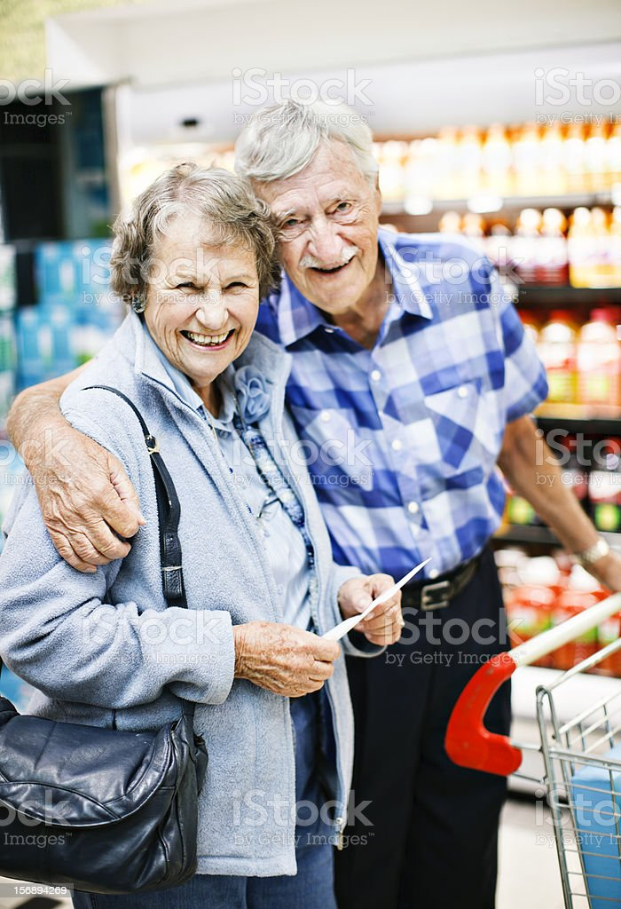 Happy, affectionate senior couple shopping in supermarket stock photo