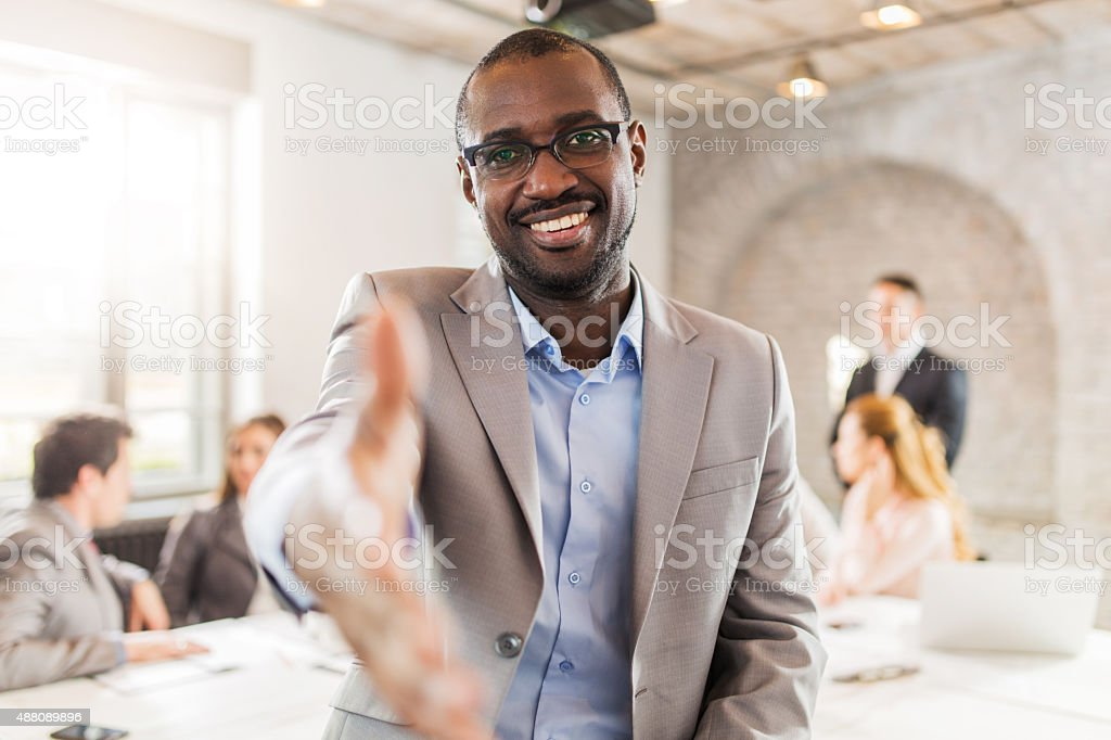 Happy African American businessman offering a handshake. stock photo