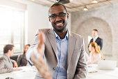 Happy African American businessman offering a handshake.
