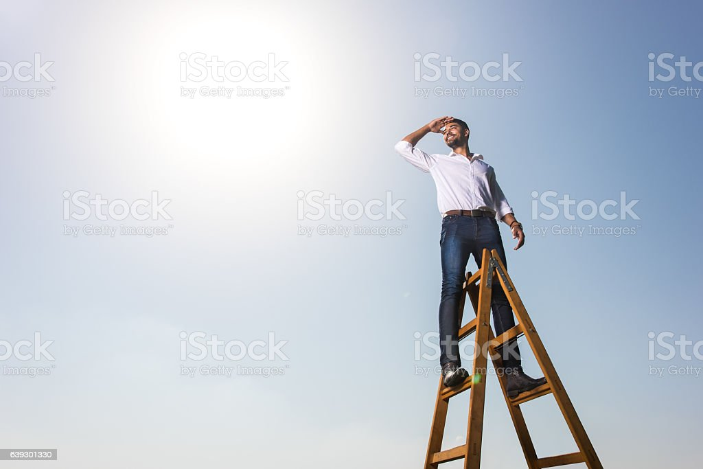 Happy African American businessman on the ladders against the sky. stock photo