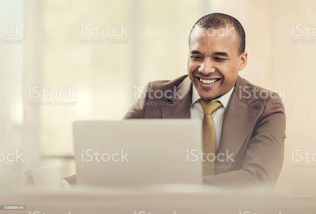 Happy African American businessman working on laptop in the office. stock photo