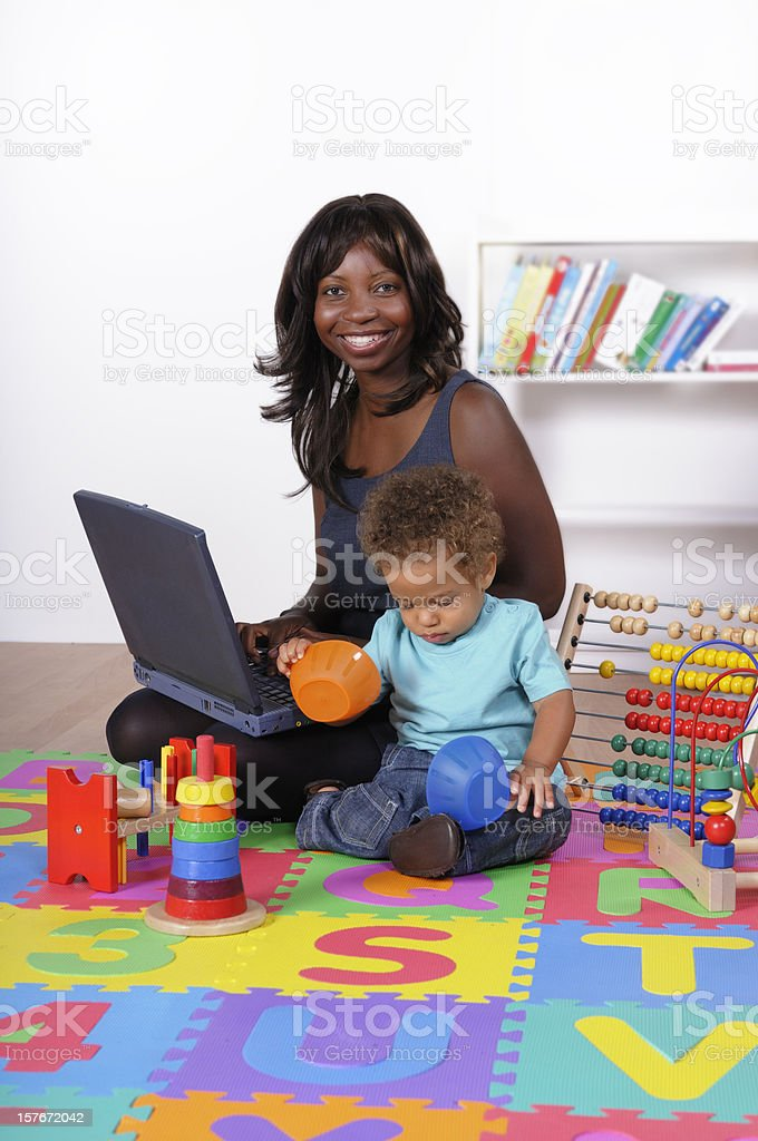 Happy African American Businesswoman Integrating Work And Childacre stock photo