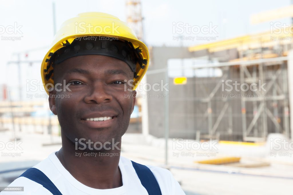 Happy african american construction worker at building site stock photo