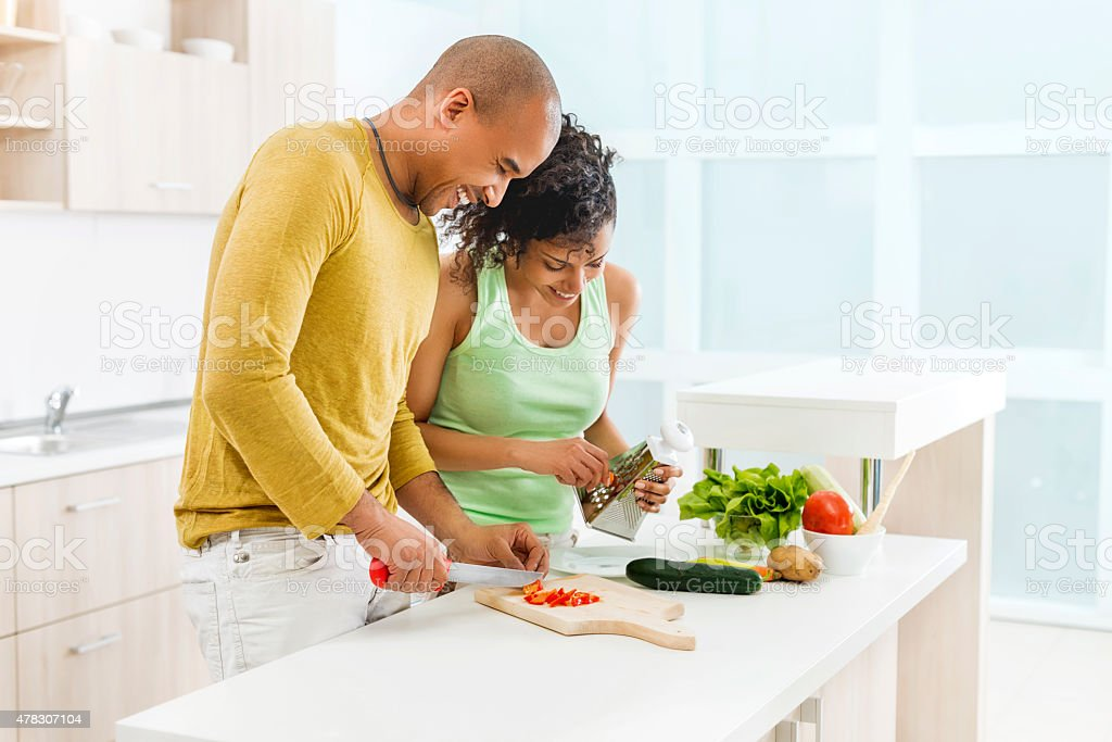 Happy African American couple making salad in the kitchen. stock photo