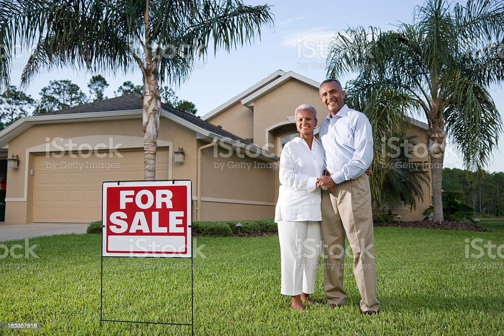 Happy African American couple outside house with for sale sign stock photo