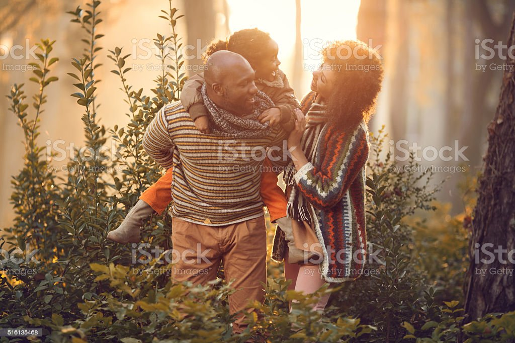Happy African American family at sunset in autumn park. stock photo