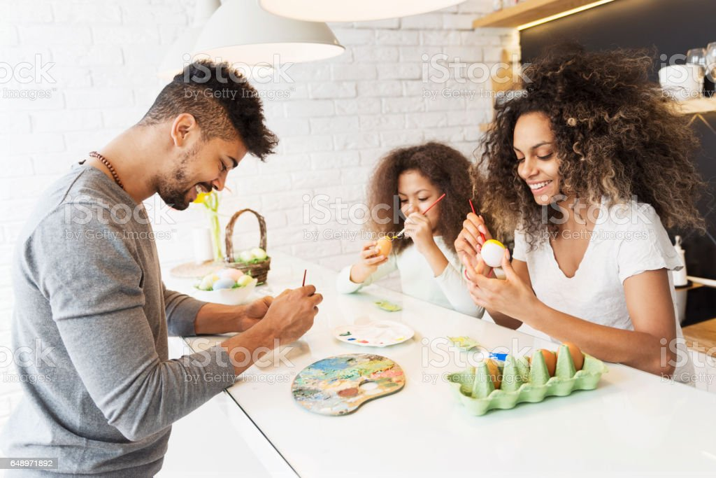 Happy African American family coloring Easter eggs stock photo