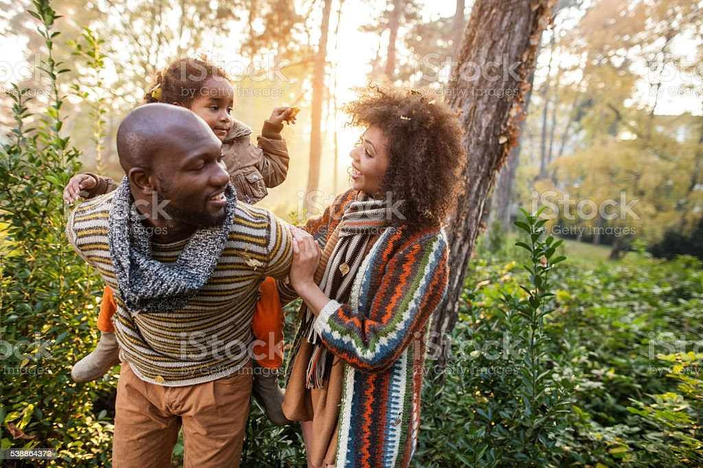 Happy African American family communicating at sunset during autumn. stock photo