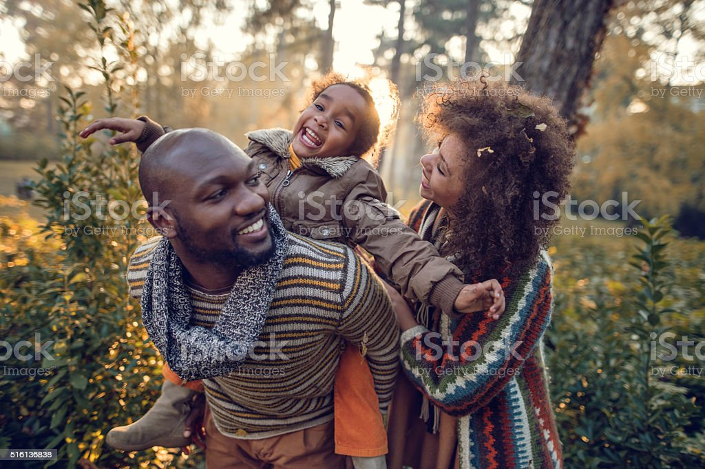 Happy African American family having fun in nature. stock photo
