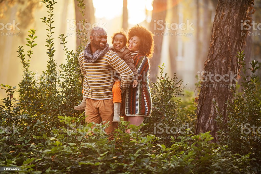 Happy African American family in nature at sunset. stock photo