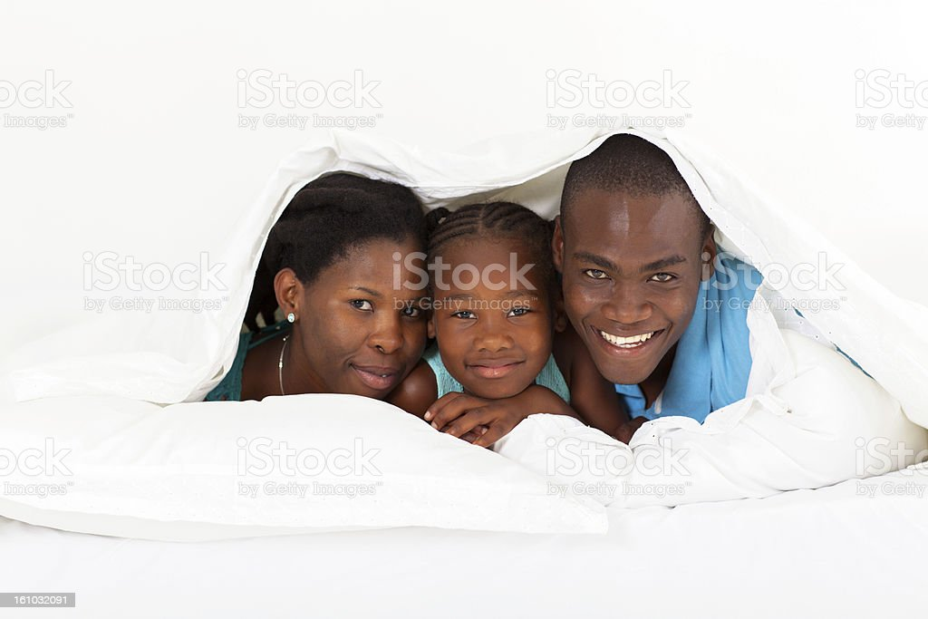 happy african american family lying under duvet stock photo