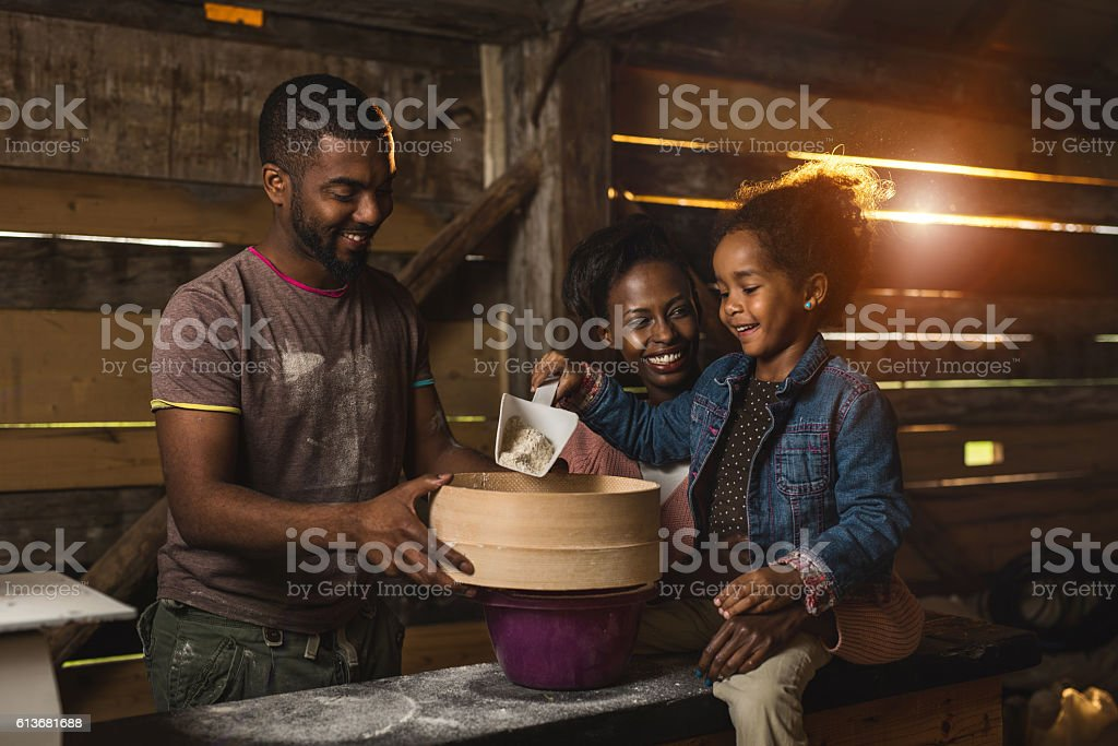 Happy African American family working together in a mill. stock photo