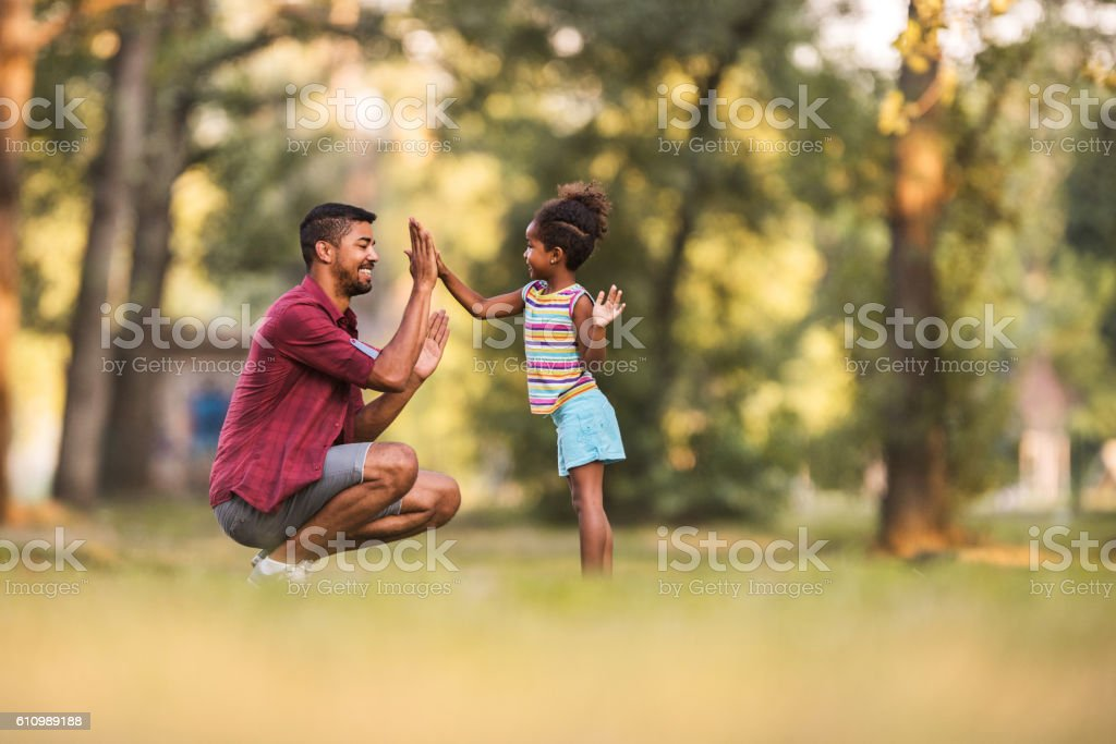 Happy African American father and daughter playing clapping game outdoors. stock photo