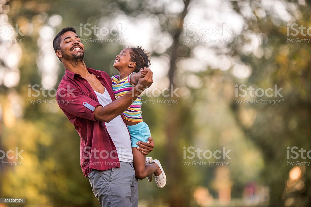 Happy African American father dancing with his cute daughter outdoors. stock photo