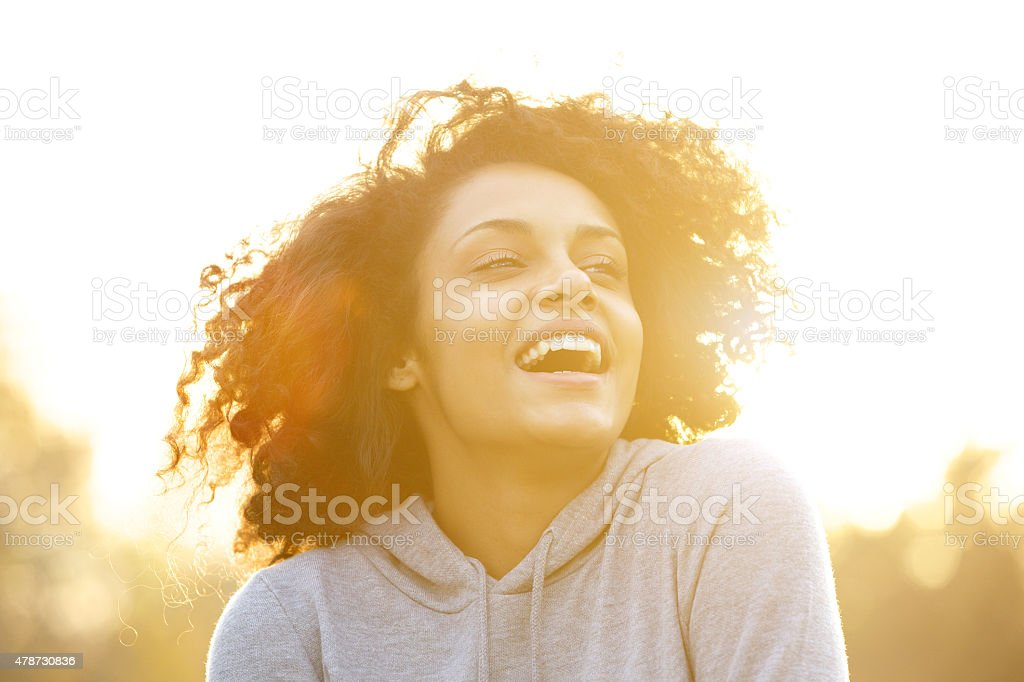 Happy african american girl laughing outdoors stock photo