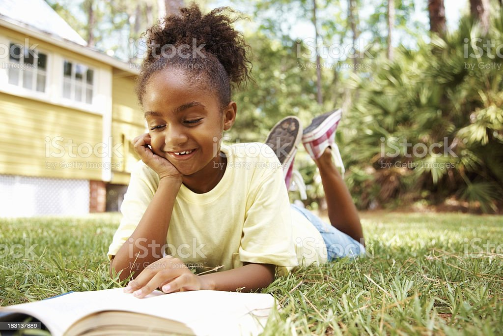 Happy African American girl reading book while lying on lawn royalty-free stock photo