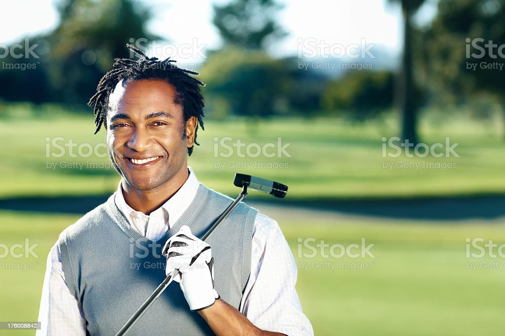 Happy African American golfer holding a club royalty-free stock photo