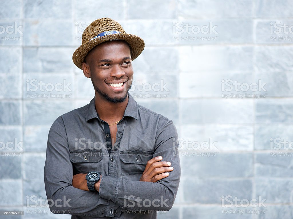 Happy african american guy smiling with arms crossed stock photo