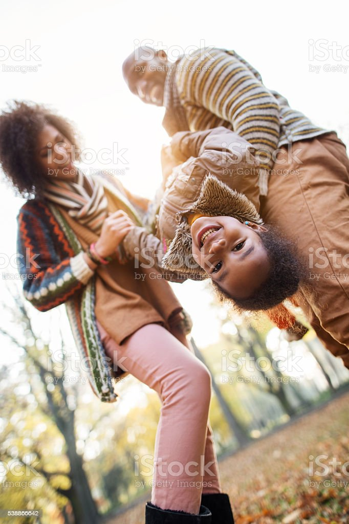 Happy African American little girl having fun with parents outdoors. stock photo