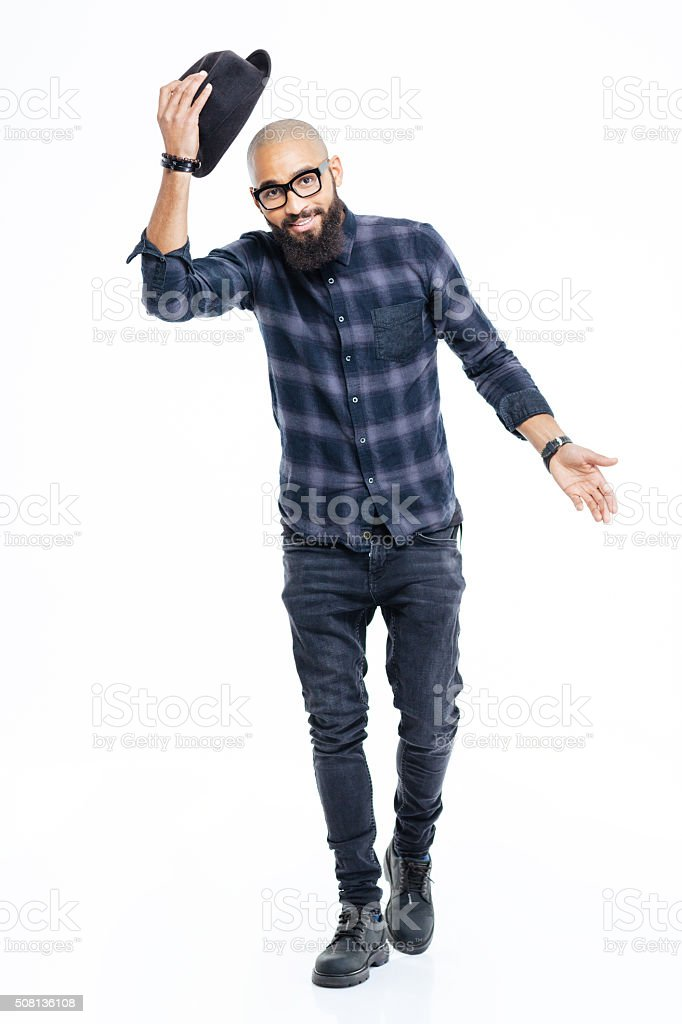 Happy african american man greeting and taking off his hat stock photo