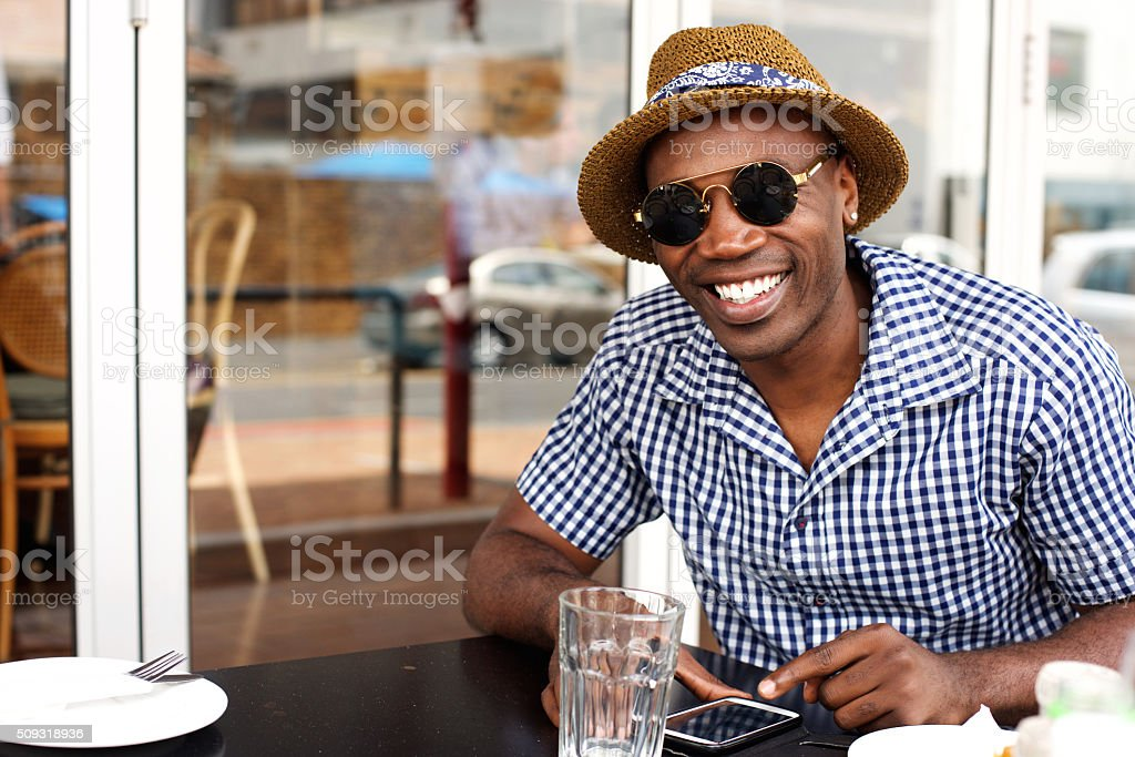 Happy african american man sitting at cafe with mobile phone stock photo