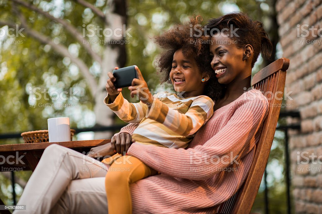 Happy African American mother and daughter taking a selfie outdoors. stock photo