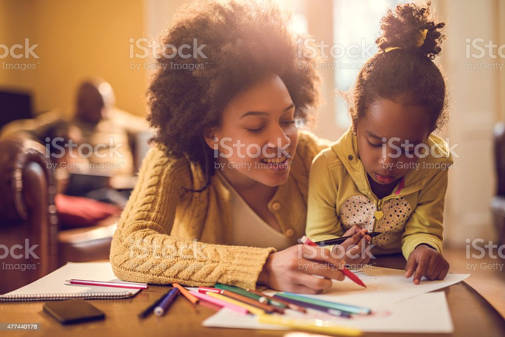 Happy African American mother assisting her daughter in coloring. stock photo