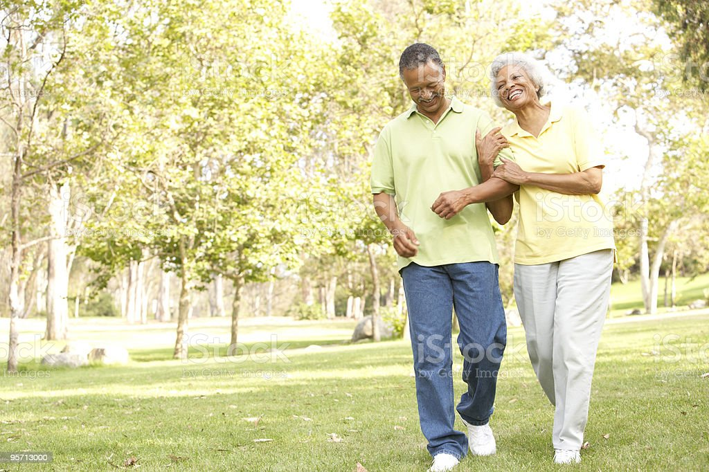 Happy African American senior couple walking in the park royalty-free stock photo