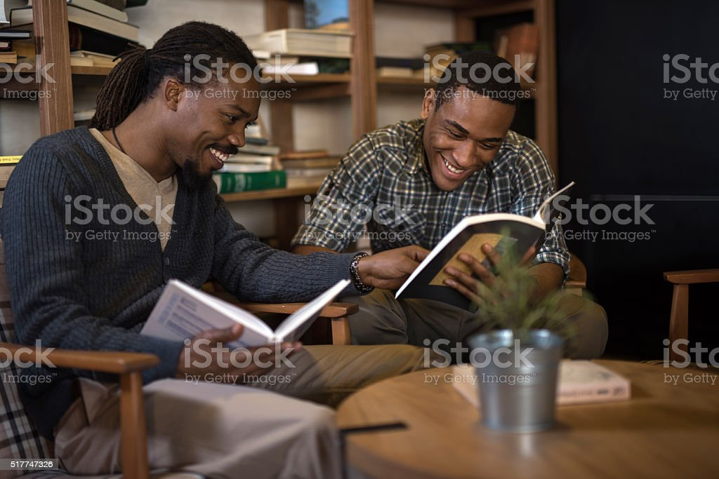 Happy African American students studying together in library. stock photo