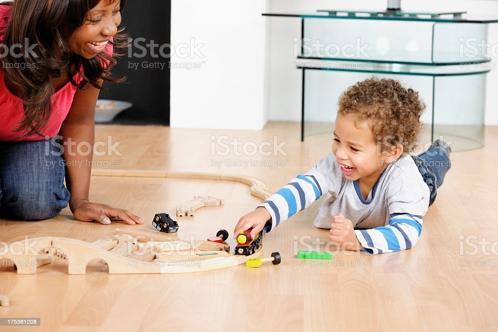 Happy African American Woman/ Carer And Toddler Playing With Trains stock photo