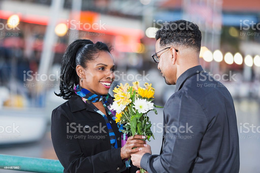 Happy African American woman getting flowers stock photo