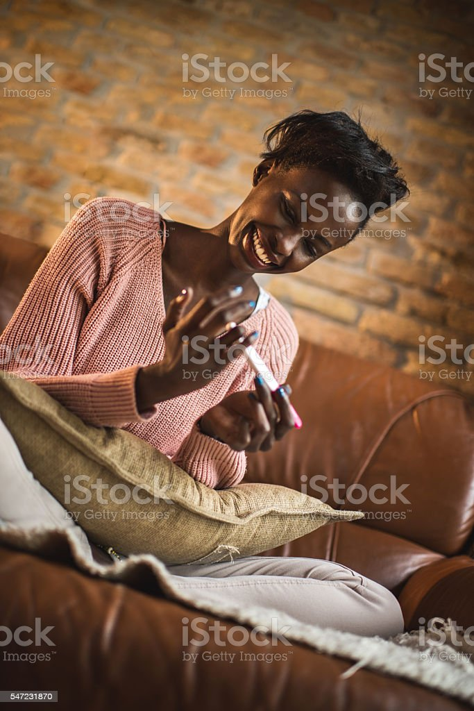 Happy African American woman having a manicure at home. stock photo