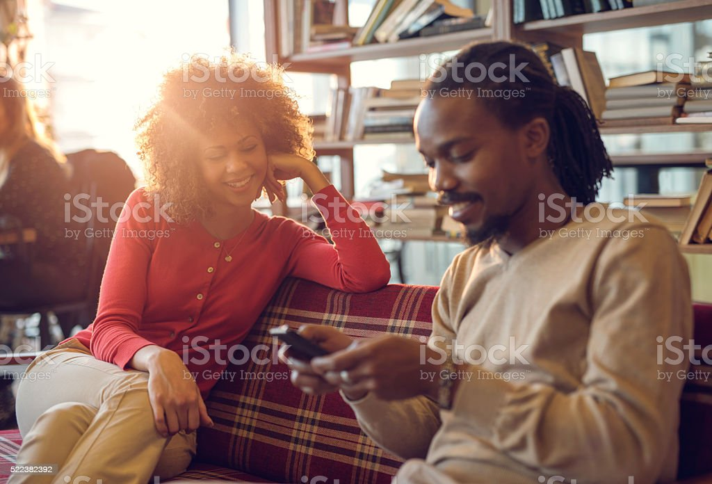 Happy African American woman looking at her boyfriend using phone. stock photo
