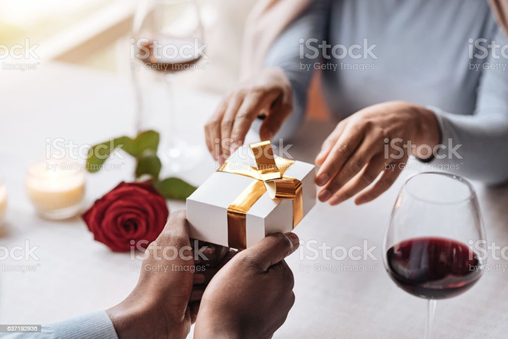 Happy African American woman opening the box from her boyfriend stock photo