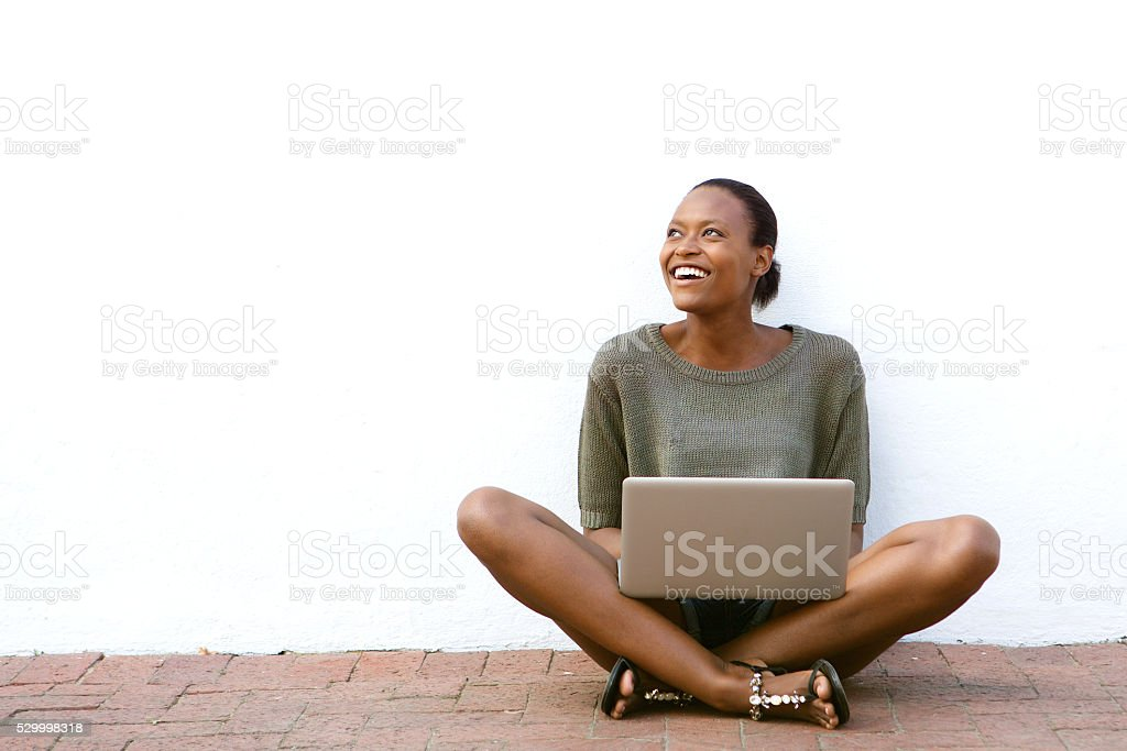 Happy african american woman sitting with laptop stock photo