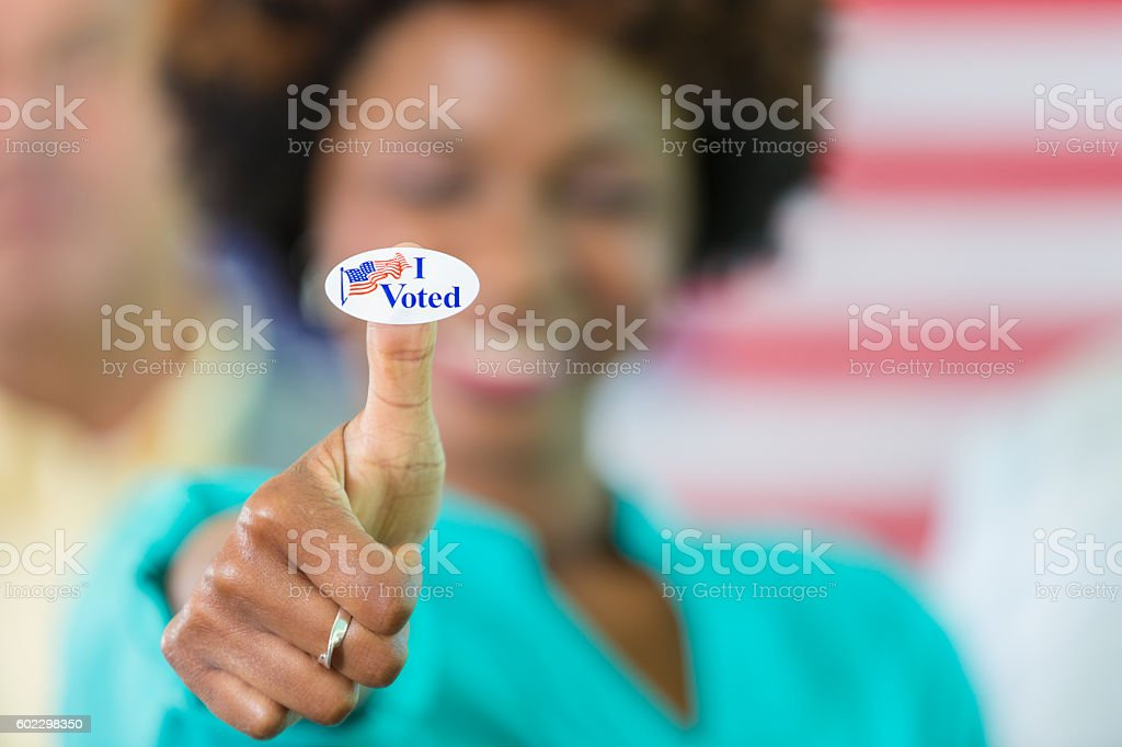 Happy African American woman with an I Voted sticker stock photo