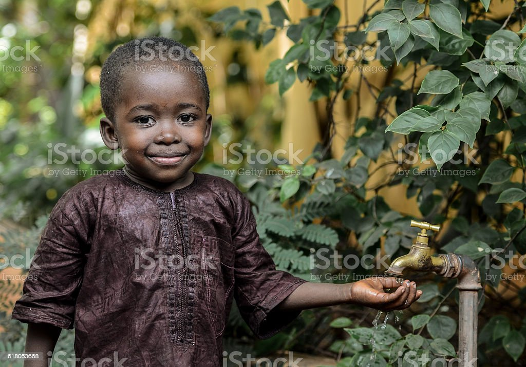 Happy African Boy Finally Gets Access to Clean Healthy Water stock photo