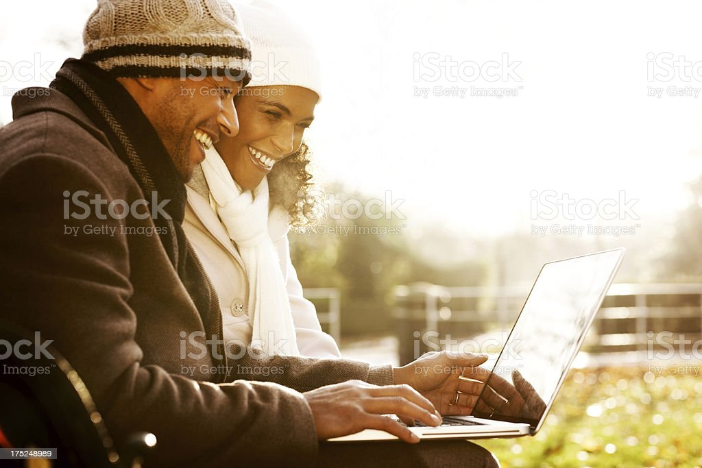 Happy African couple using laptop on an autumn day royalty-free stock photo