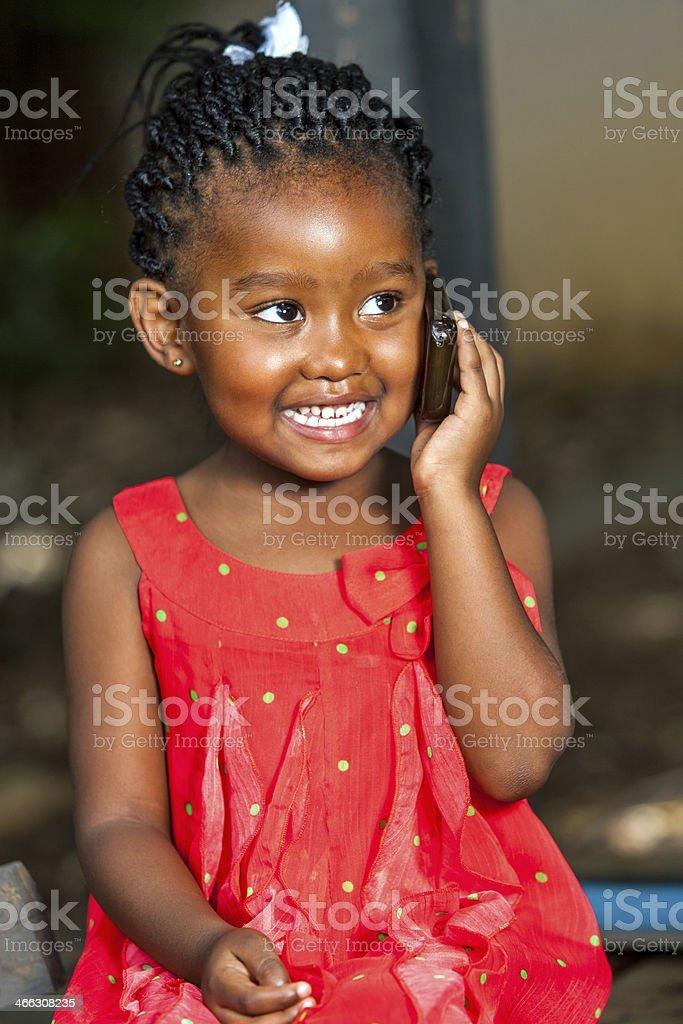 Fille africaine heureuse parle sur téléphone intelligent. photo libre de droits