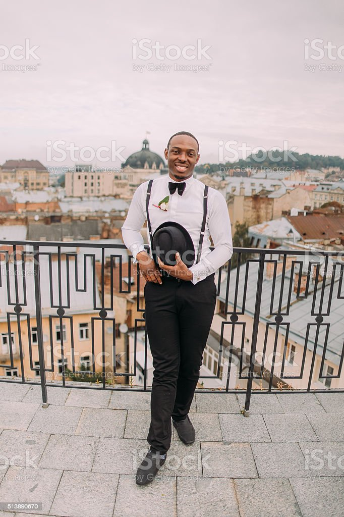 Happy african groom smiling on the rooftop stock photo