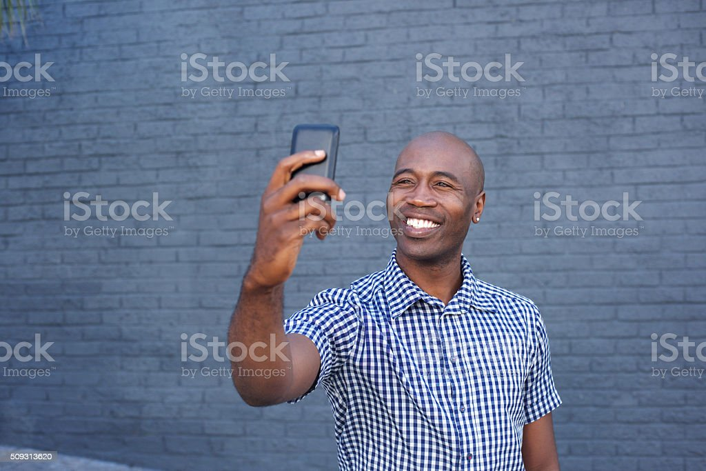 Happy african guy taking a selfie with his cell phone stock photo
